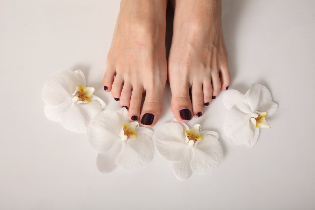 White orchid flowers female feet pedicure